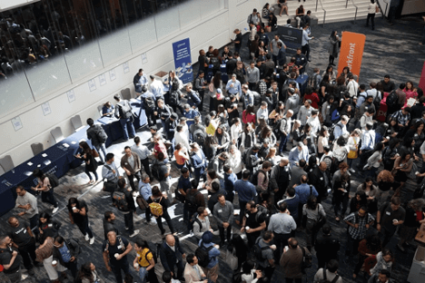 Photographic image that is looking down on a group of around 100 people at a business event. It may be a networking conference. They are all wearing name badges. There are tables with information for people to pick up and read.