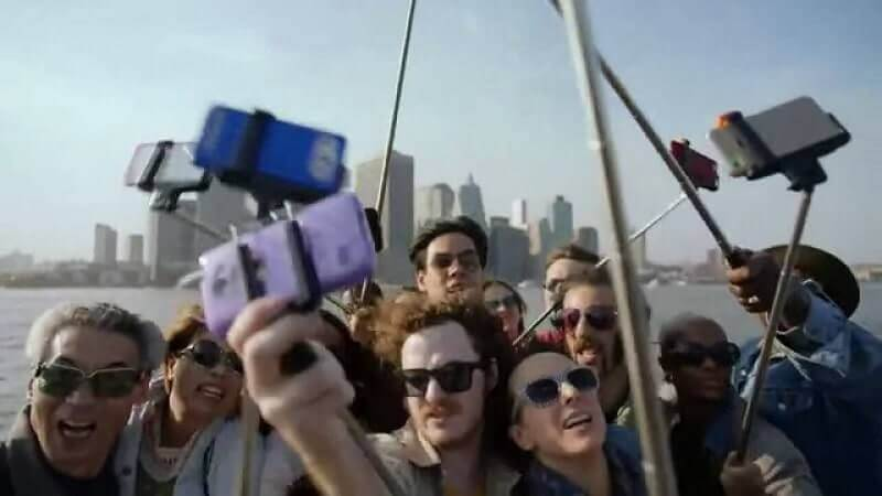 Photograph of a group of around 10 people using selfie sticks. They are taking selfies of themselves in front of the New York skyline. They are all wearing sunglasses.