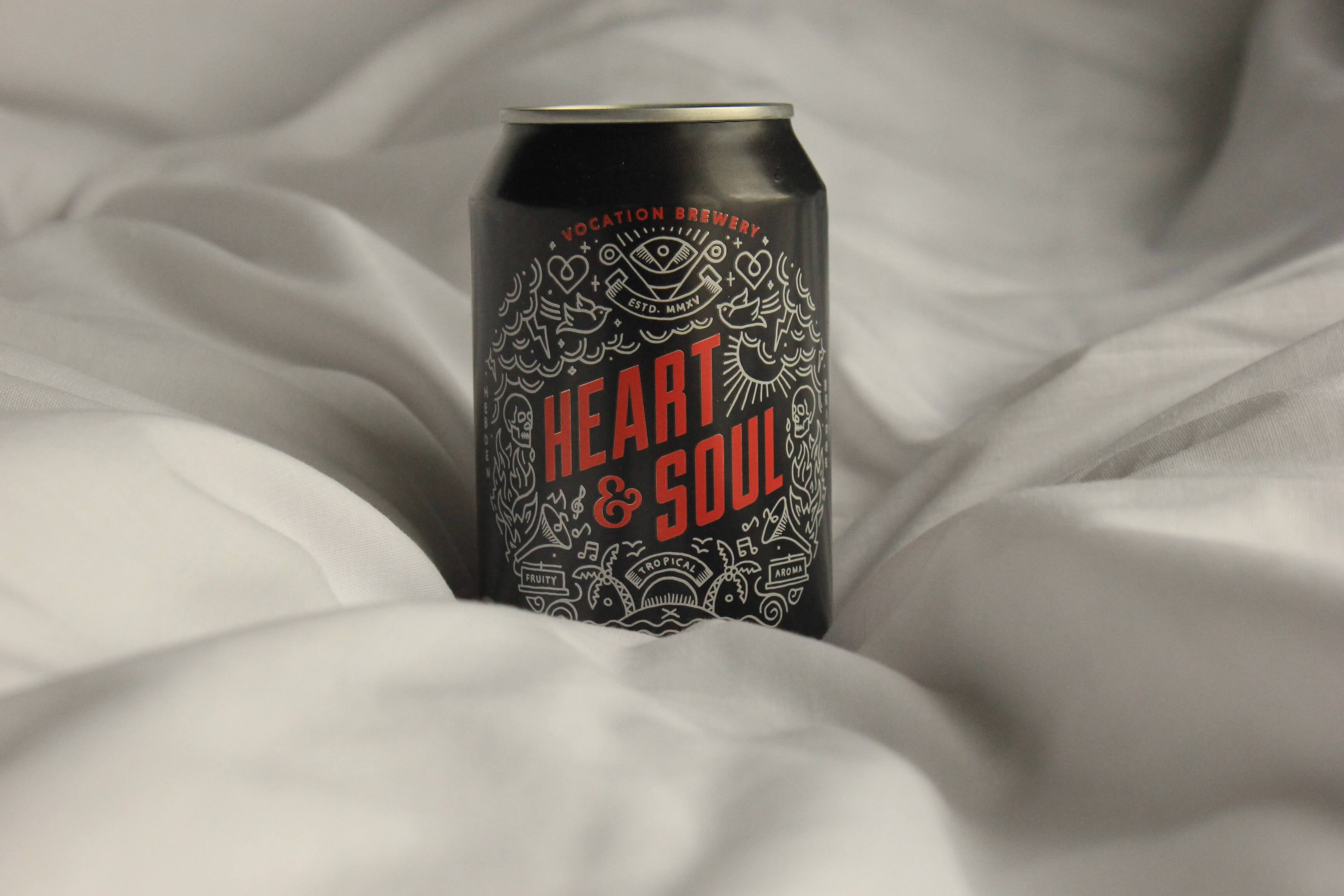 Photograph of a can of soda with the brand name Heart & Soul. The can is black, the logo and writing is red with white illustrations.