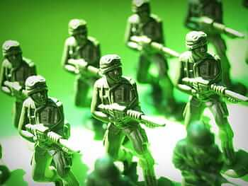Photograph of toy soldiers posed with guns drawn.