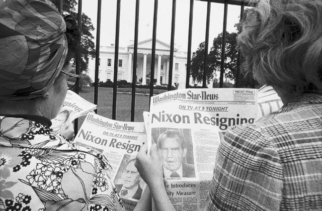 Two women in front of the White House reading about the Watergate scandal. It is the 1970s. The photograph is black and white.