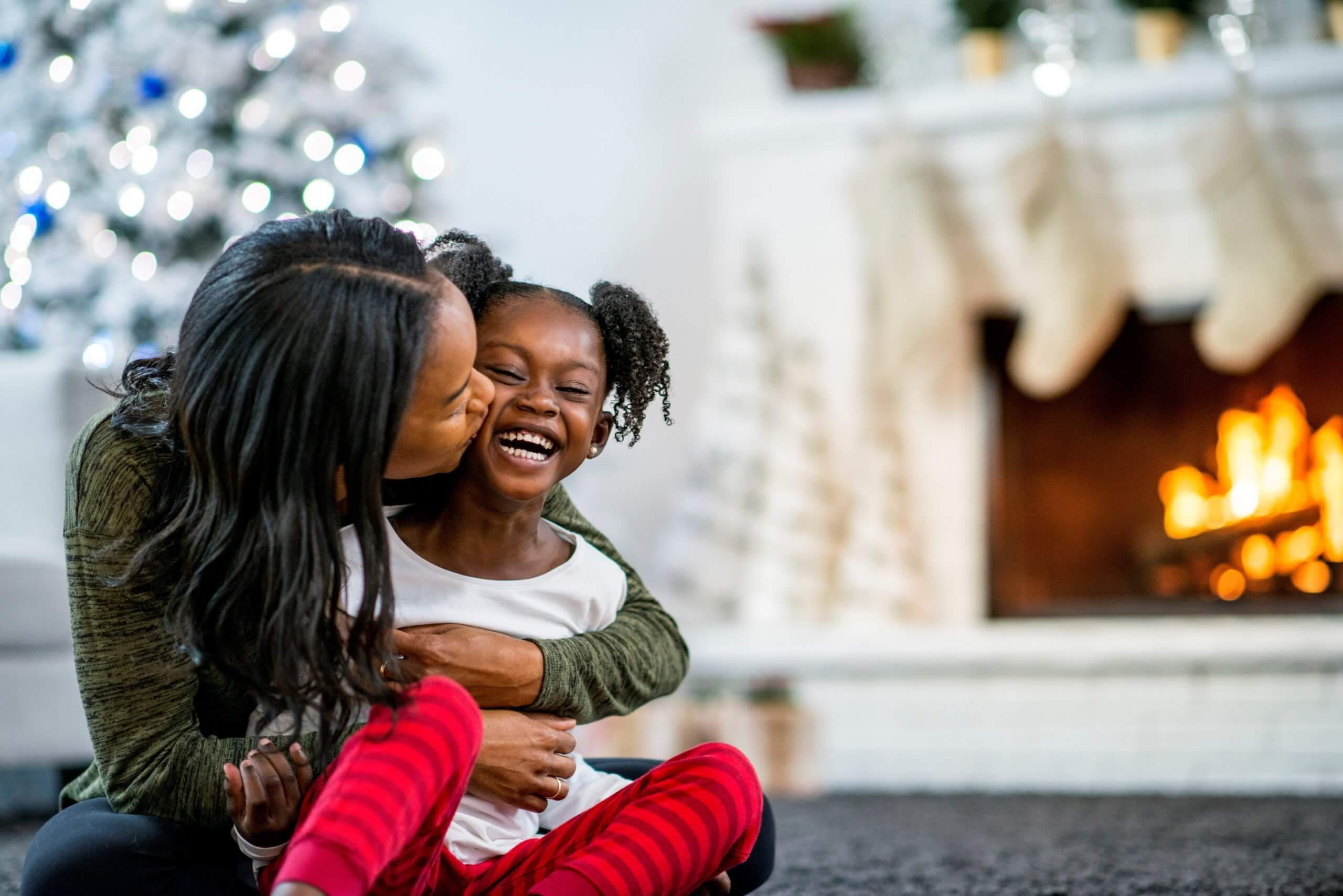 Photograph of mother and daugher hugging in front of a Christmas tree. There is a log fire with stocking hanging up in the background of the picture.
