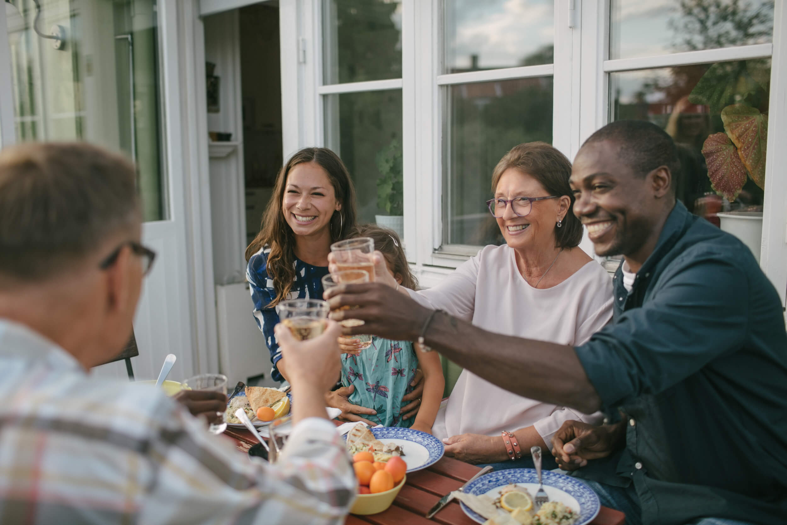 Group of 4 people eating outside and raising glasses. There are 2 women and a man to the right facing the camera, and a man with his back to the camera on the left. They are multi generational.
