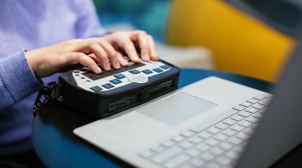 Two hands using a screenreadeer.