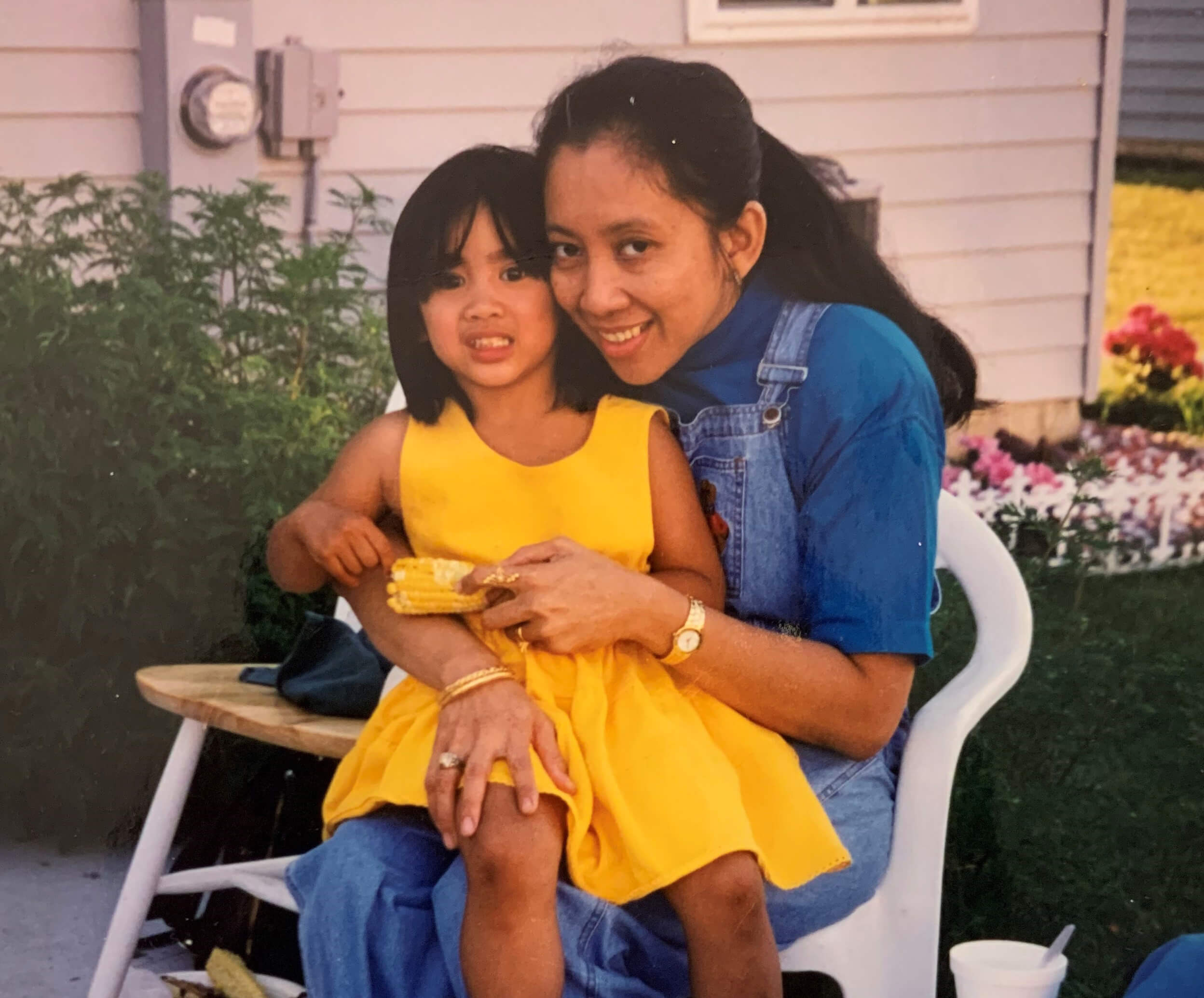 Photograph of a mother and young daughter sitting cuddling on a chair. The mother is on the right, the little girl on the left. The girl is wearing a yellow dress. They look happy.