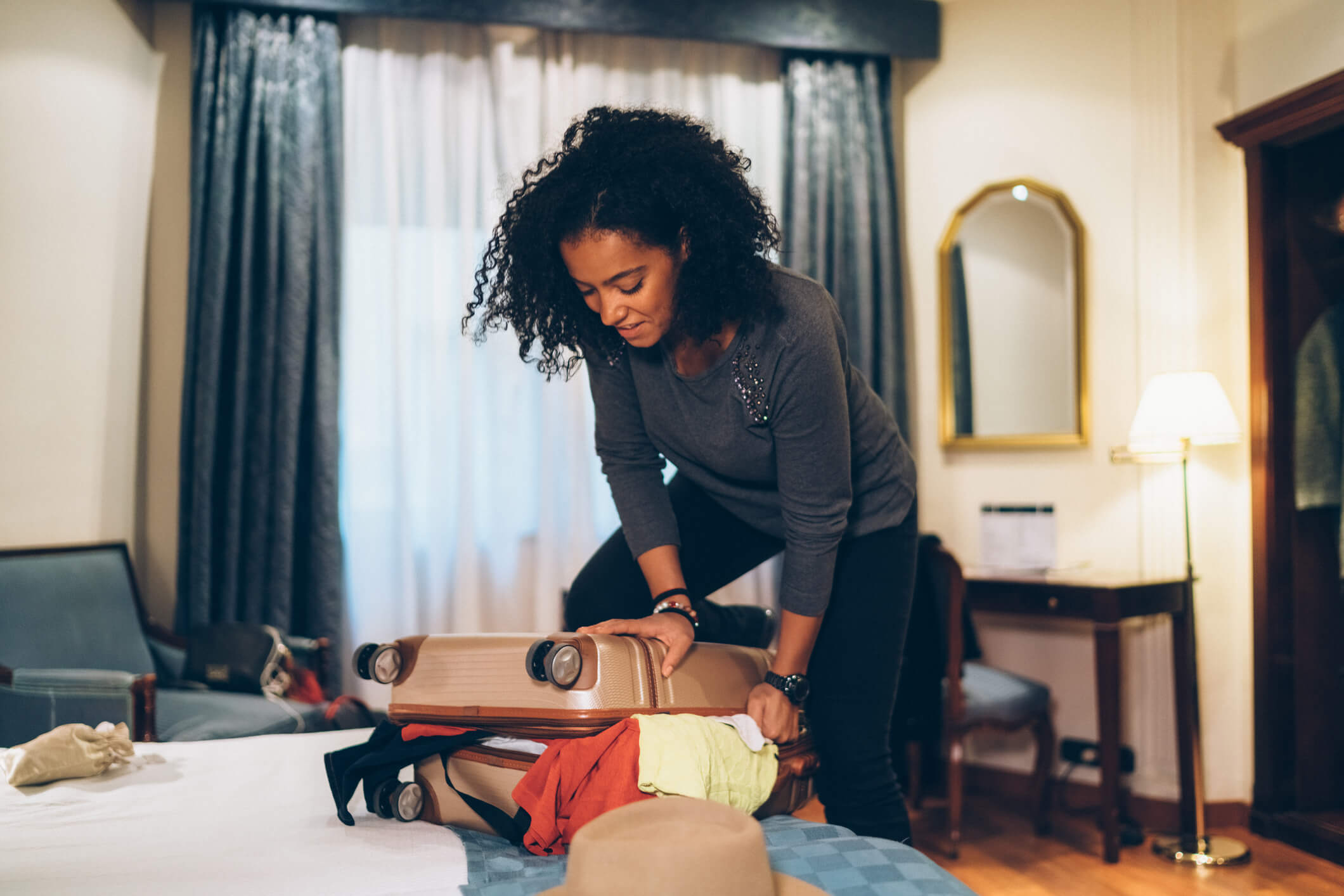 Young black woman trying to close a very full suitcase. She is in her bedroom.