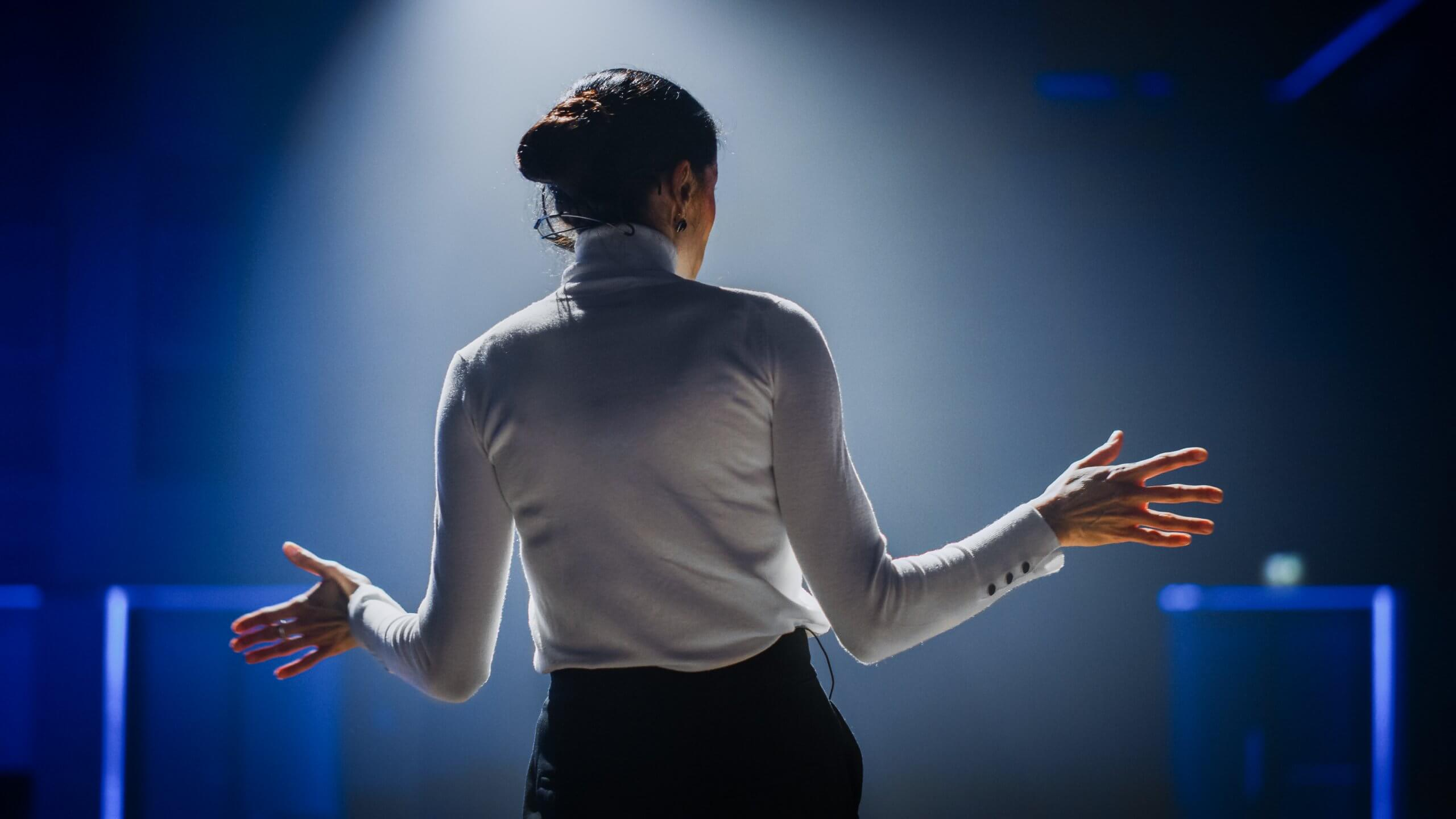 A business woman stood with her back to the camera presenting to an audience.