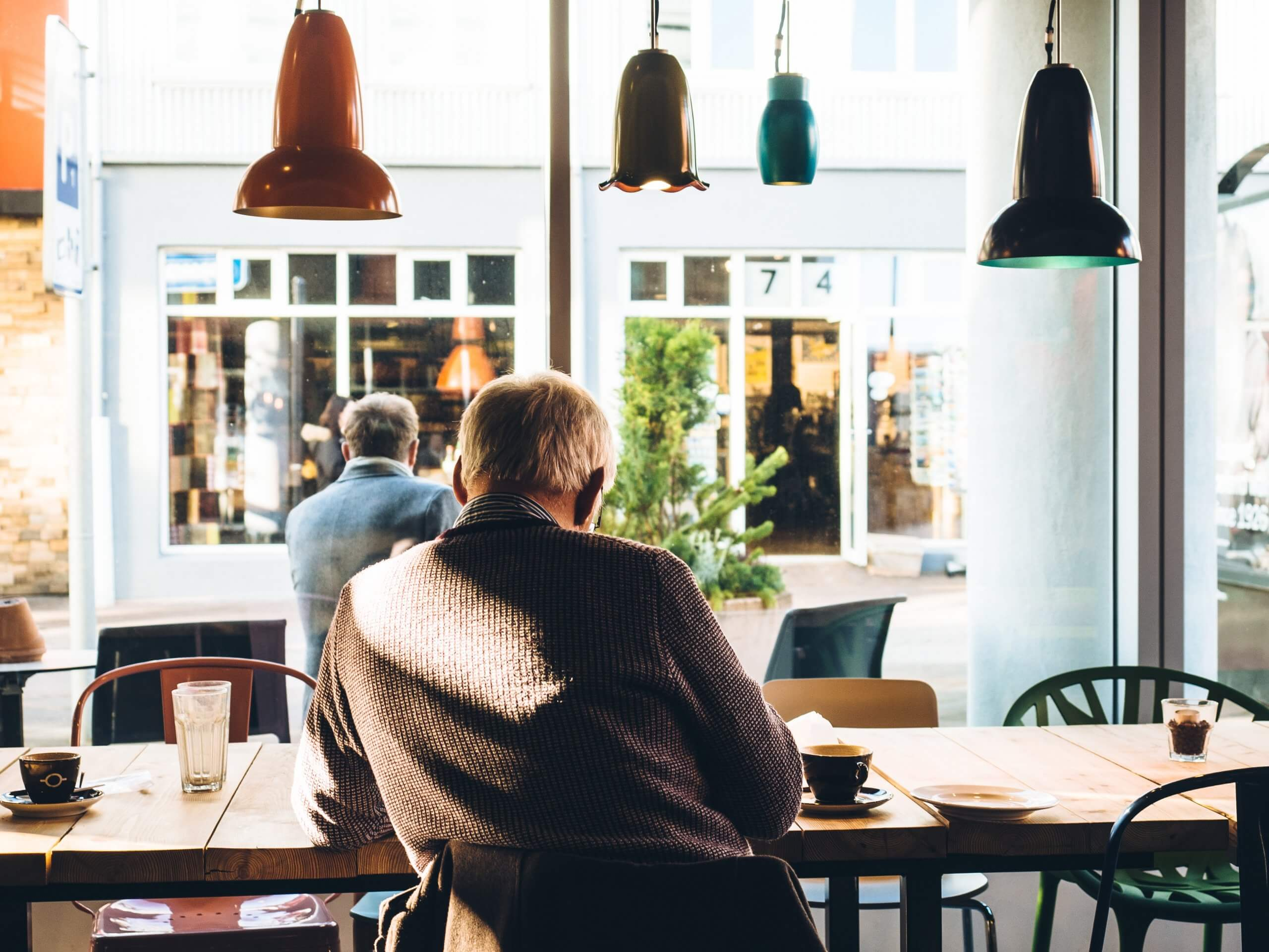 Image of an elderly man sat at a coffee table looking out of a window. He seems to be in a cafe.