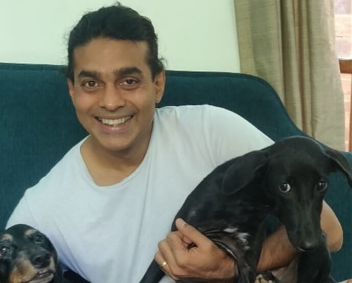 Smiling man with 2 black dogs on his knee.