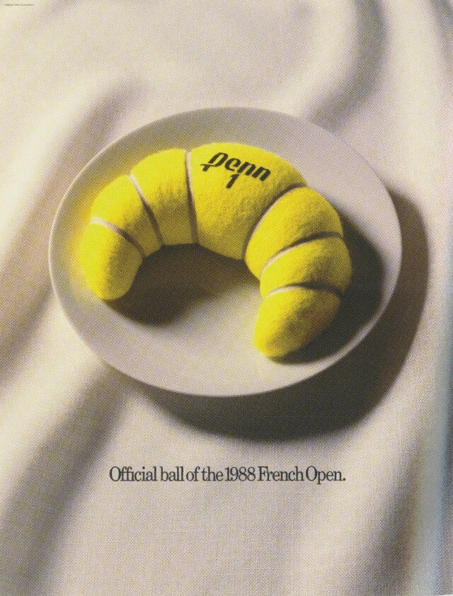 Yellow tennis ball on a white plate. The tennis ball is shaped like a croissant.