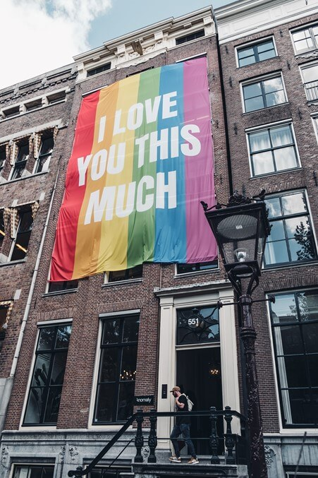 Brick building with a large rainbow Pride flag hanging down the front.