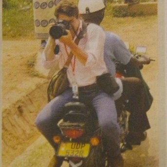 Man on the back of a motorbike pointing a long range camera lens at the photographer.