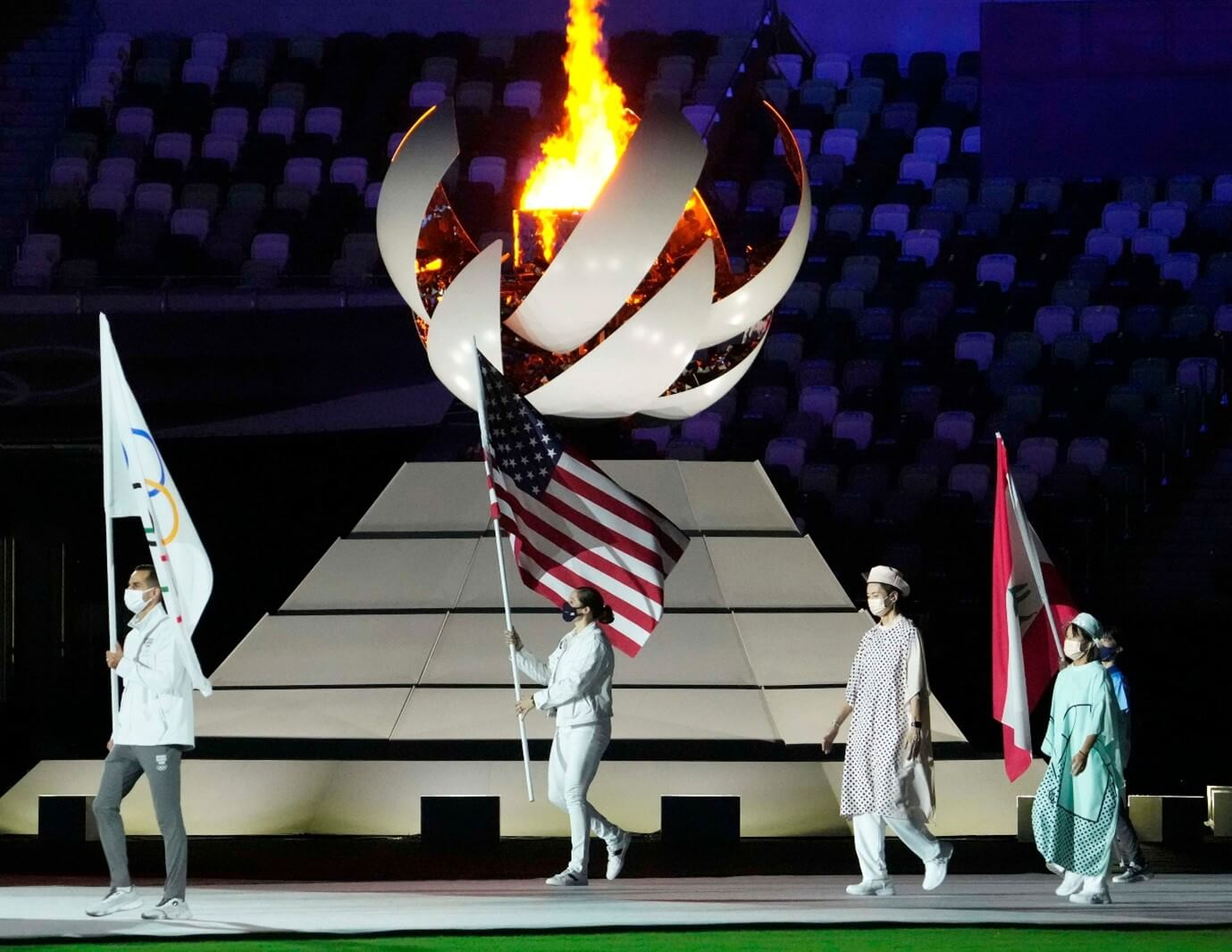 Olympics closing ceremony with four figures in white in front of the Olympic flame. One is holding up the american flag.