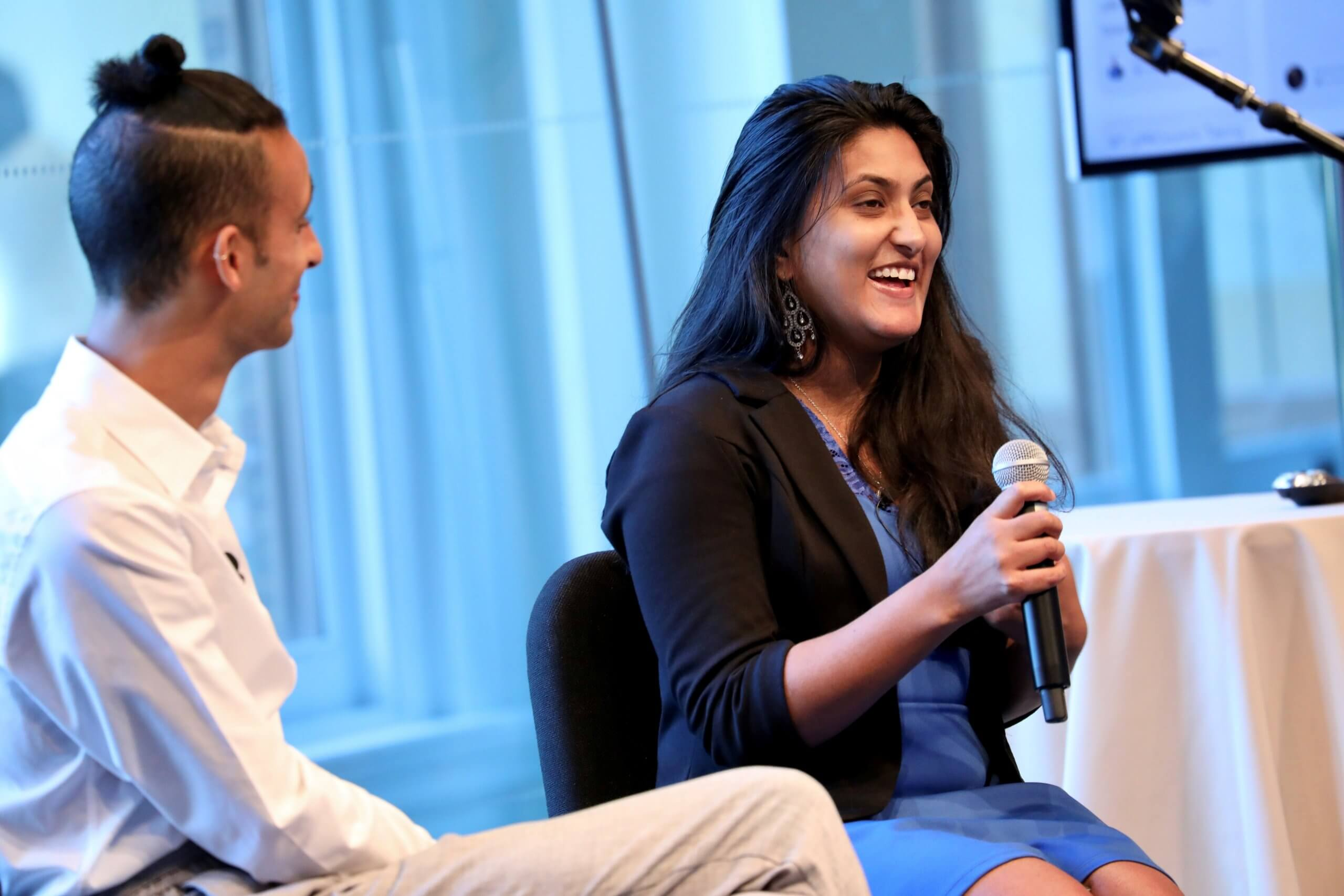 A man and woman talking at a conference. Sena Pottackal is the woman talking on the right hand side. She is holding a microphone.